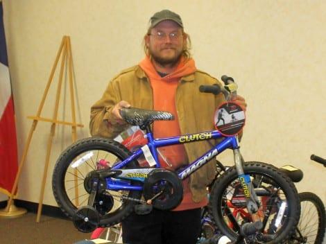 Blake Hesch with a new bike for his son Dakota, a kindergarten student at Crenshaw School.
