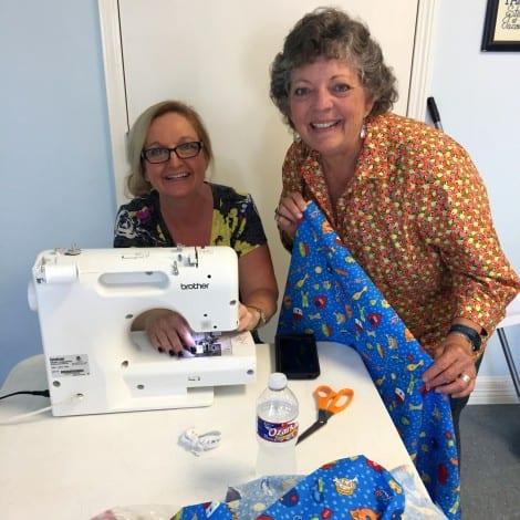 Rita Moseley cuts it up.  Elaine Rollfing sews it up.